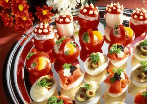 Stuffed eggs & tomatoes as snacks on serving platter